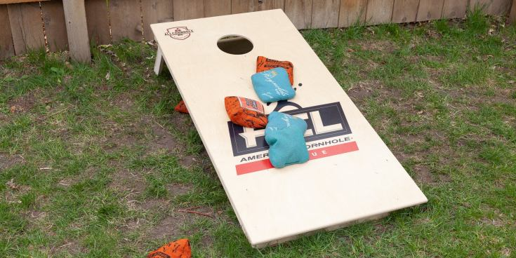 AllCornhole board and GameChanger bags set in a grass-covered backyard.
