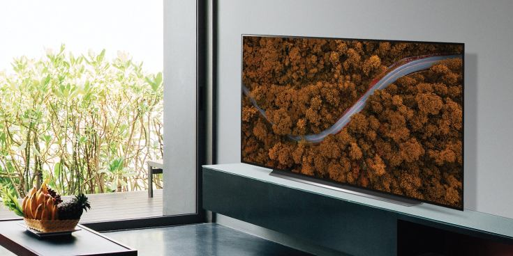 An LG OLED TV mounted on a wall in a living room setting