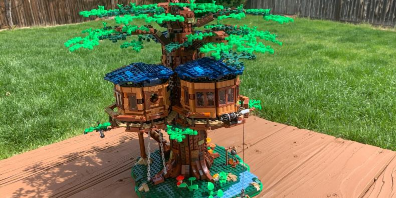 A lego tree house set, being displayed outside in a backyard setting.