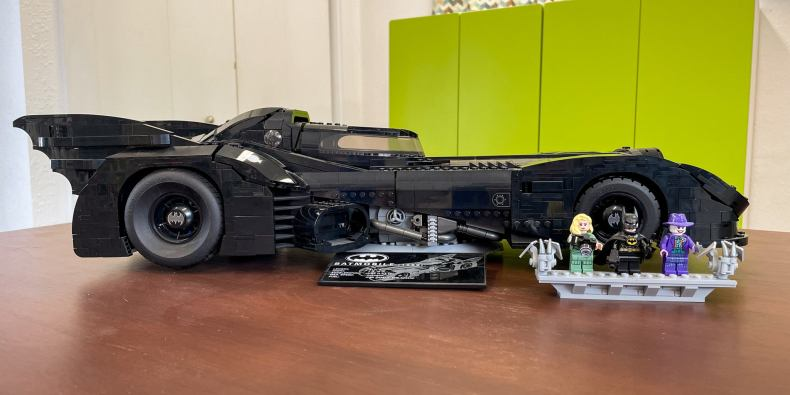 A lego version of the batmobile, pictured from the side, next to lego versions of three batman characters.