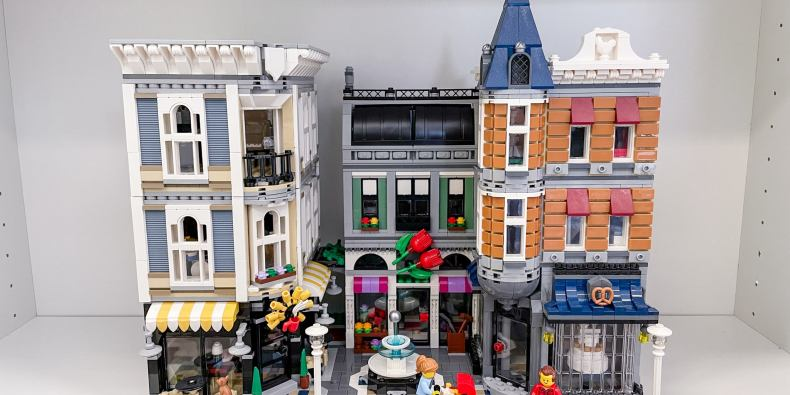 The lego assembly square set, comprised of a lego city square with a fountain, surrounding shops and lego citizens.
