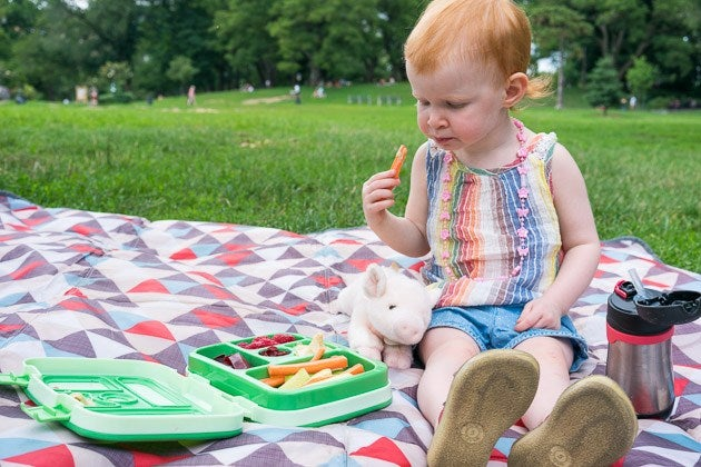 A child eating food from the Bentgo Kids Lunch Box in a park.