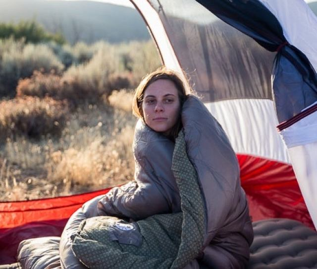 A Woman Sitting In A Tent Wrapped Up In Our Pick For Best Car Camping Sleeping