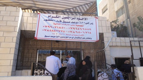 A banner outside the locked offices of Nidaa Al-Kheir asks refugees to schedule an appointment before arriving to pick up aid packages (photo credit: Elhanan Miller/Times of Israel)