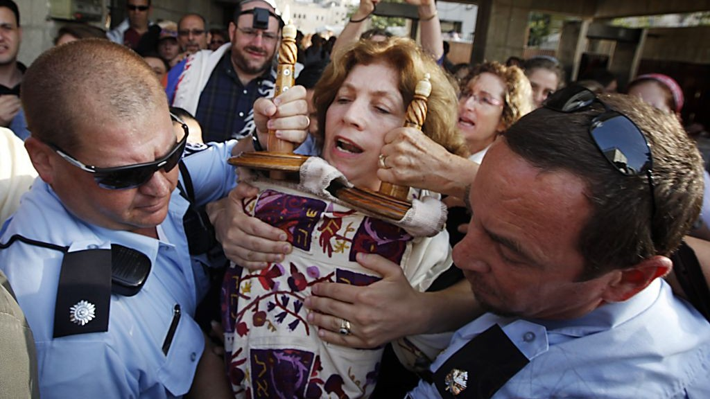 Police escort Anat Hoffman holding a Torah scroll from the Western Wall, on July 12, 2010. (Miriam Alster/Flash90)