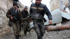 Des rebelles syriens transportent un lance-roquettes lors de combats contre l'armée, le 27 janvier 2014 à Alep