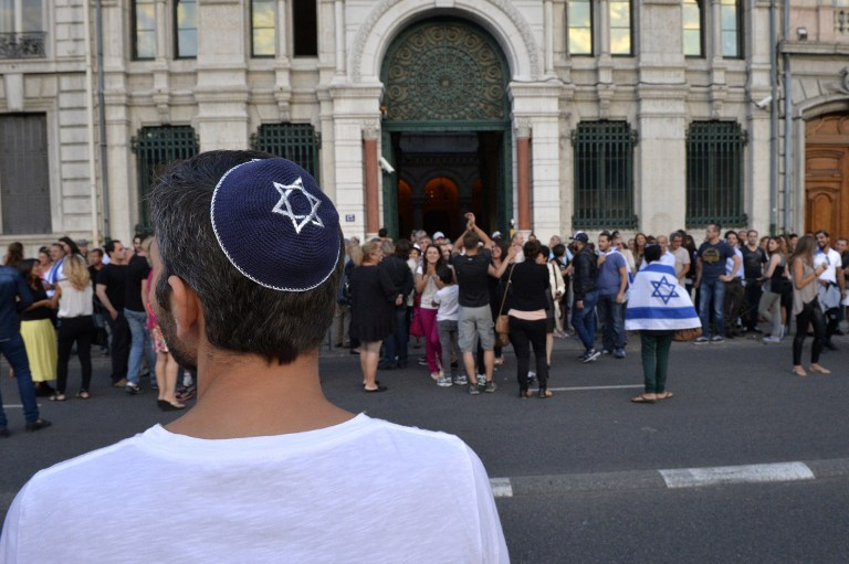A man wearing a skullcap looks on as people take part in a demonstration called by the Representative Council of Jewish Institutions in France on July 31, 2014, in front of a Lyon synagogue. (AFP/Romain LaFabregue)