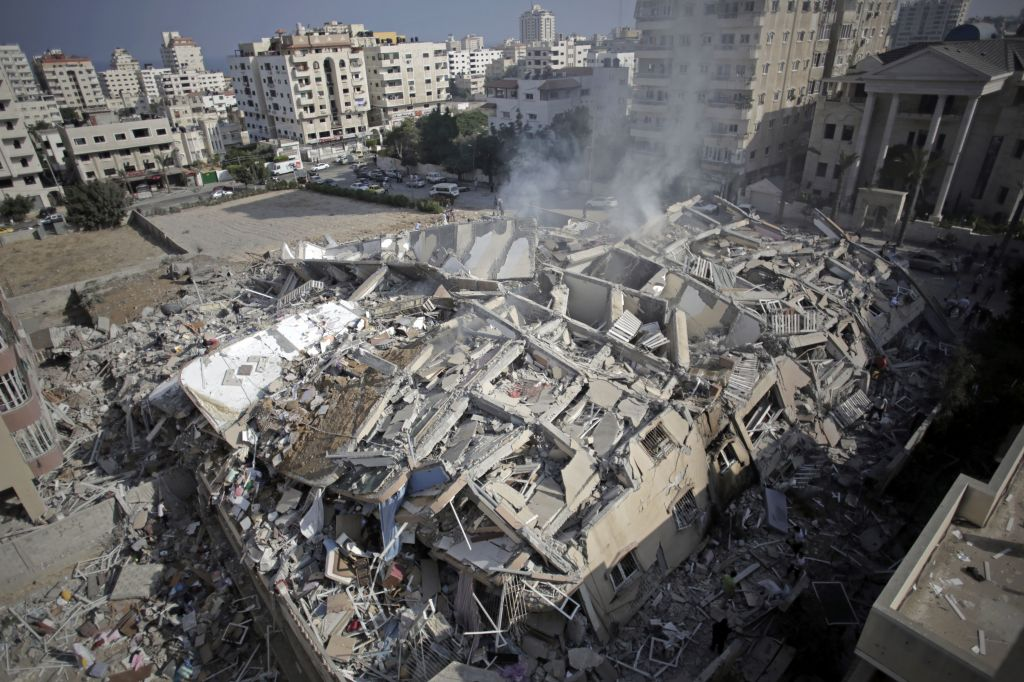 Smoke rises from the rubble of the al-Zafer apartment tower following Israeli airstrikes Saturday that collapsed the 12-story building, in Gaza City, Sunday, August 24, 2014. (AP/Khalil Hamra)