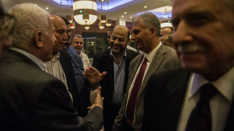 Hamas deputy leader Moussa Abu Marzuk (C) shakes hands with head of the Palestinian delegation Azzam al-Ahmed (L) upon their arrival at a Cairo hotel after a meeting with senior Egyptian intelligence officials, August 11, 2014 (photo credit: AFP/ Khaled Desouki)