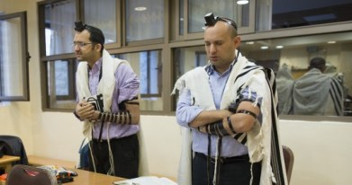 Economy Minister Naftali Bennett (R) prays inside a synagogue where two terrorists from East Jerusalem killed five people on Tuesday. November 19, 2014. (photo credit: Yonatan Sindel/Flash90)