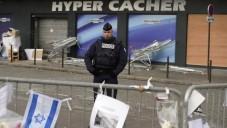 Un policier montant la garde le 21 janvier 2015 devant l'épicerie Hyper Casher où quatre Juifs ont trouvé la mort, le 9 janvier 2015, tués par Amédy Coulibaly à Paris. (Crédit : AFP/ ERIC FEFERBERG)