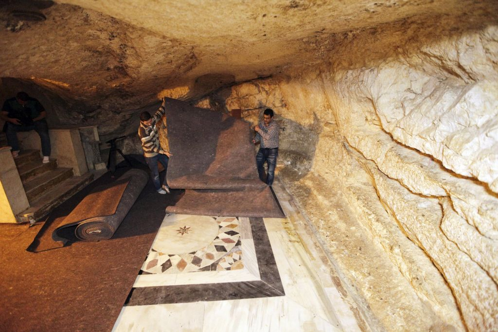 In this Sunday, April 19, 2015 photo, workers place carpets over ancient floor designs in the cave under the Dome of the Rock shrine in Jerusalem. The Dome of the Rock enshrines the large rock slab where Muslim tradition says Mohammed ascended to heaven. Jews believe the rock may be where the holiest part of the two ancient temples stood about 2,000 years ago. (photo credit: AP/Mahmoud Illean)