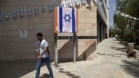 """An Israeli man walks past the Orange company logo covered with an Israeli flag at the """"Partner Orange"""" Communications Company's offices in the city of Rosh Haayin, Israel. Thursday, June 4, 2015. (AP Photo/Dan Balilty)"""