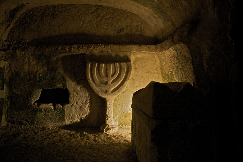An emblem of a menorah carved in the stone, inside a structure at Beit She'arim National Park, an archaeological site in the Lower Galilee. (Doron Horowitz/Flash90)