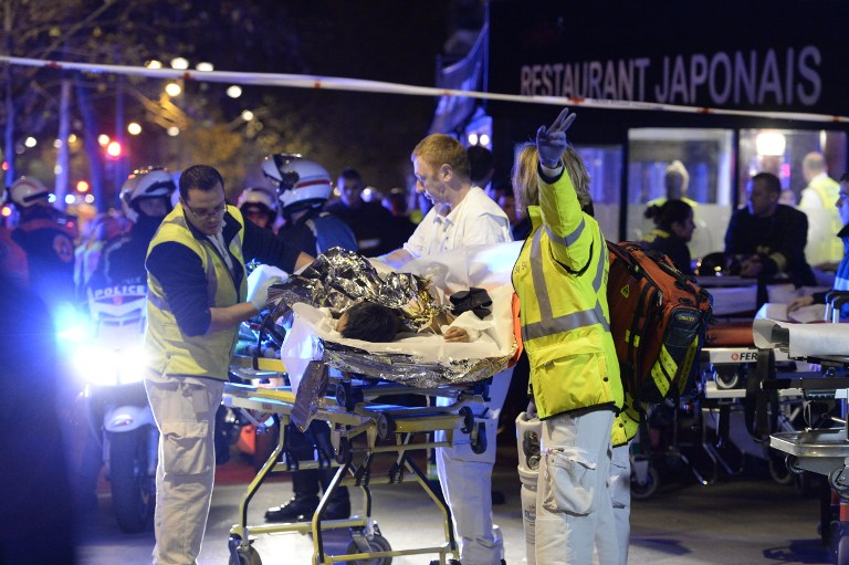 Rescuers evacuate an injured person near the Bataclan concert hall in central Paris, early on November 14, 2015. (AFP PHOTO/MIGUEL MEDINA)