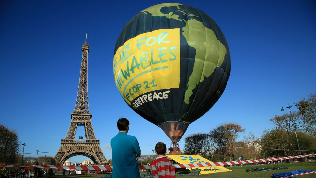 Boys look at a hot air balloon of the environmental group Greenpeace, near the Eiffel Tower ahead of the 2015 Paris Climate Conference, in Paris, Saturday, Nov. 28, 2015. (AP Photo/Thibault Camus)