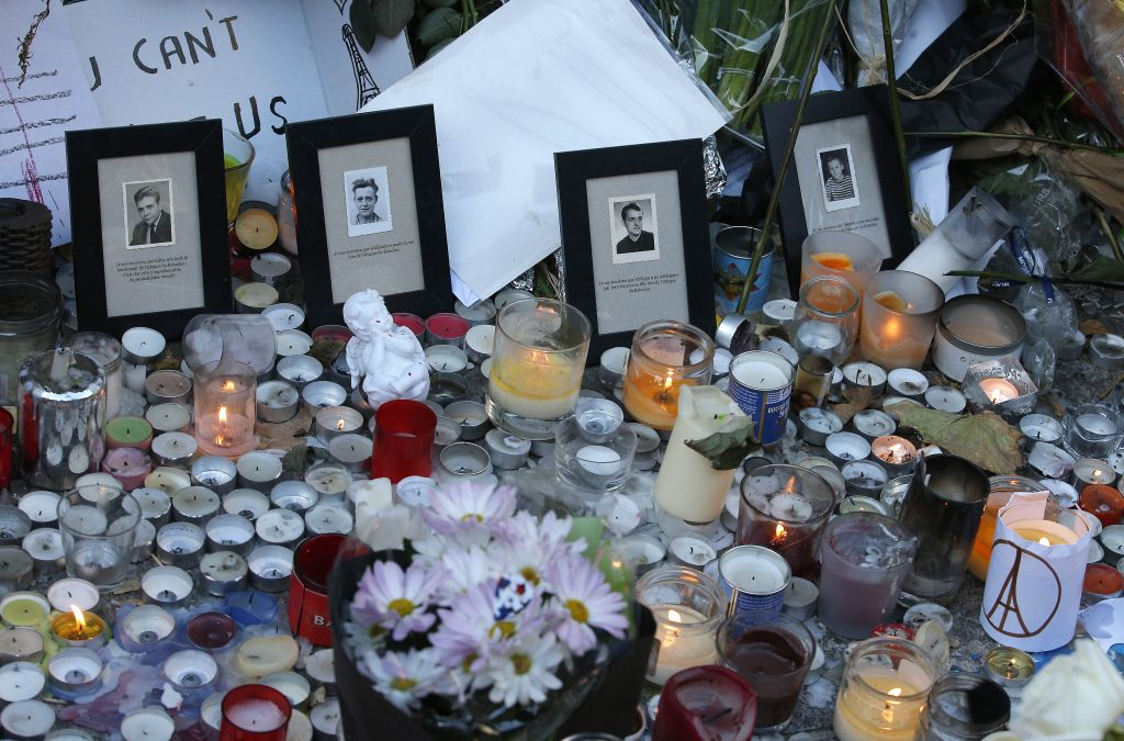 Pictures of victims are placed behind candles outside the Bataclan concert hall in Paris, Sunday, Nov. 15, 2015. (AP Photo/Christoph Ena)
