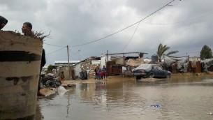 Des Palestiniens près d'une route inondée d'eau de pluie suite aux fortes pluies, à Khan Yunis dans le sud de Gaza le 24 janvier 2016 (Crédit : Abed Rahim Khatib / Flash90)