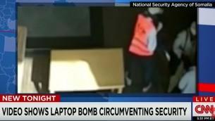 Deux hommes, dont au moins un est un employé de l'aéroport, tendant ce qui ressemble à un ordinateur portable au terroriste kamikaze présumé, après son passage des contrôles de sécurité à l'aéroport de Mogadiscio. (Crédit : capture d'écran YouTube/CNN)