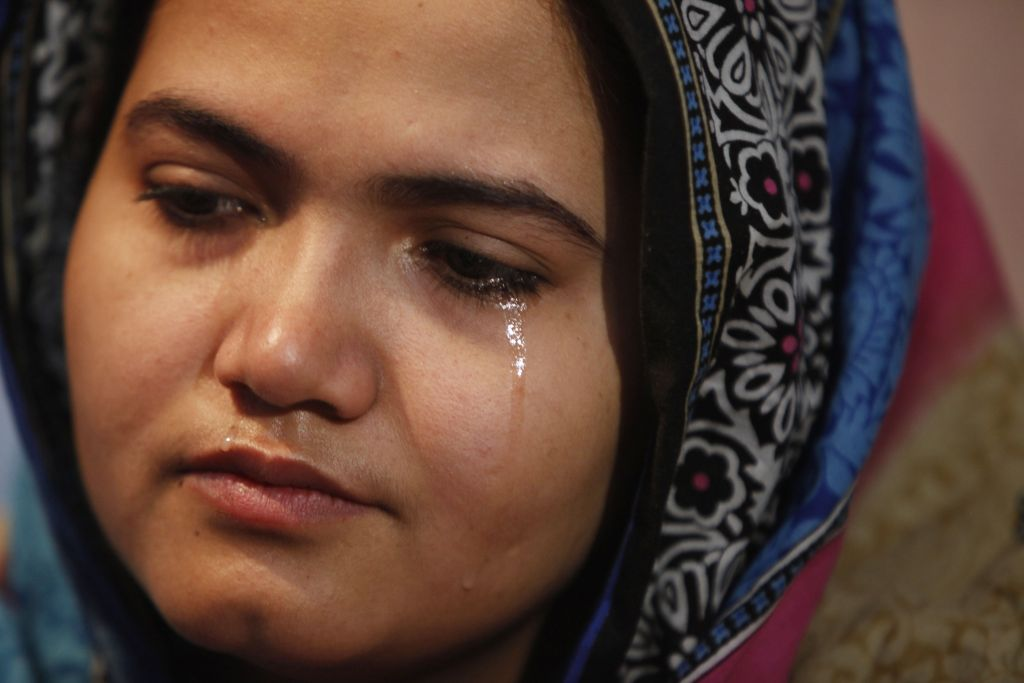 In this photo taken on Jan. 26, 2016, Kainaat Soomro weeps during an interview with The Associated Press in Karachi, Pakistan. She was 13 years old and on her way to buy a toy for her newborn niece when three men kidnapped her, held her for several days and repeatedly raped her. Eight years later, she is still battling for justice. (AP Photo/Shakil Adil)
