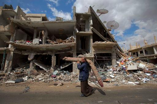 In this April 14, 2016 image, a Syrian man carries a carpet as walk through a devastated part of the town of Palmyra as families load their belongings onto a bus in the central Homs province, Syria. (AP Photo/Hassan Ammar)