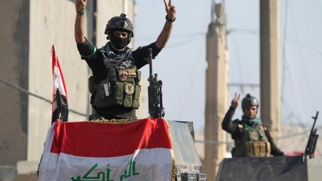 """Des membres de l'unité d'élite contreterroriste de l'Irak faisant le """"V"""" de la victoire à Ramadi après avoir repris la ville à l'Etat islamique, le 29 décembre 2015. (Crédit : AFP/Ahmad al-Rubaye)"""