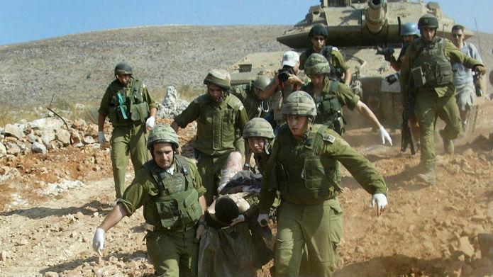 Les soldats évacuent un camarade blessé au cours de la seconde guerre du Liban, le 24 juillet 2006, (Crédit : Haim Azoulay / Flash 90)