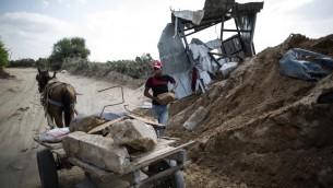 Un Palestinien mettant des pierres sur un chariot à côté d'un cratère dans Beit Lahia dans le nord de la bande de Gaza le 22 août 2016, suite à une frappe aérienne israélienne la veille qui a eu lieu la veille après la chute d'une roquette gazaouie à Sdérot. (Crédit : AFP/Mahmud Hams)