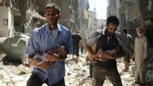 Des Syriens avec des bébés traversent les ruines de bâtiments détruits après une frappe aérienne sur le quartier tenu par les rebelles de Salihin, à Alep, le 11 septembre 2016. (Crédit : AFP/Ameer Alhalbi)