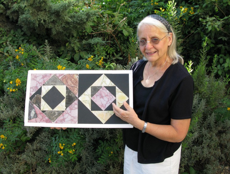 Frankie Snyder holds restored marble floor tiles based on fragments found in fill from the Temple Mount that archaeologists from the Temple Mount Sifting Project say are from the Herodian Temple in Jerusalem. (Temple Mount Sifting Project)