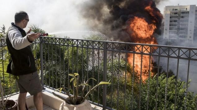 Un Israélien essaie d'éteindre un incendie d'un toit dans la ville d'Haïfa, le 24 novembre 2016 (Crédit : AFP PHOTO / JACK GUEZ