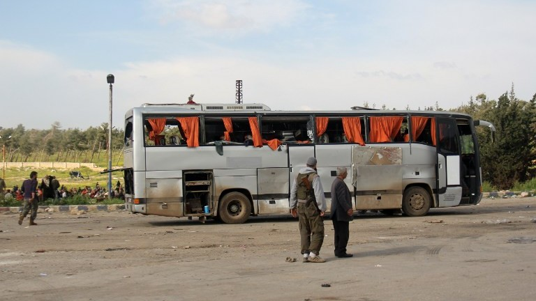 A picture taken on April 15, 2017, shows rebel fighters standing next to a damaged bus following a suicide car bombing in Rashidin, west of Aleppo. (AFP Photo/ Omar Haj Kadour)