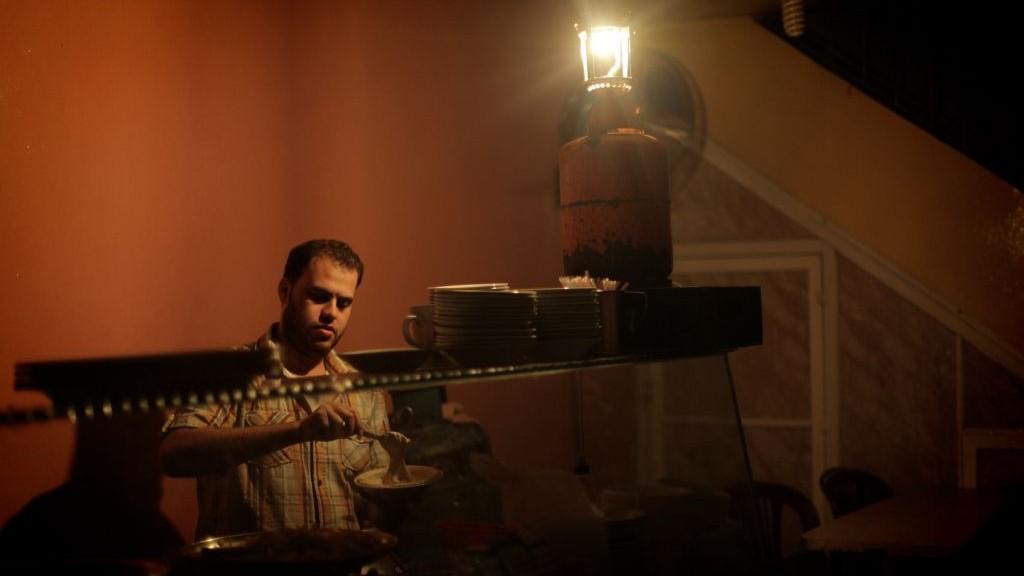 Un Palestinien utilise une lampe à gaz pour travailler dans son restaurant qui n'a plus d'électricité, dans la bande de Gaza, le 17 novembre 2013. (Crédit : Emad Nassar/Flash90)