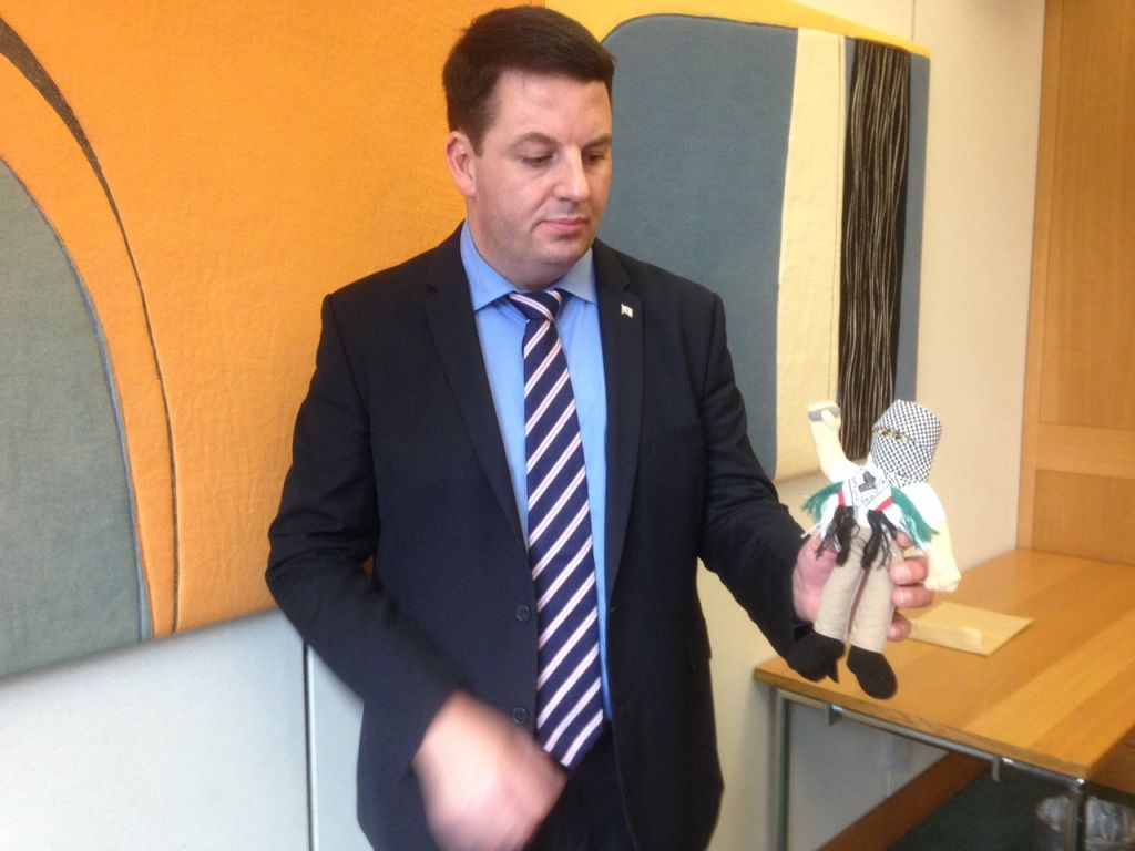 British MP Andrew Percy holds a terror doll teaching aid used in Palestinian schools. (Jenni Frazer/Times of Israel)