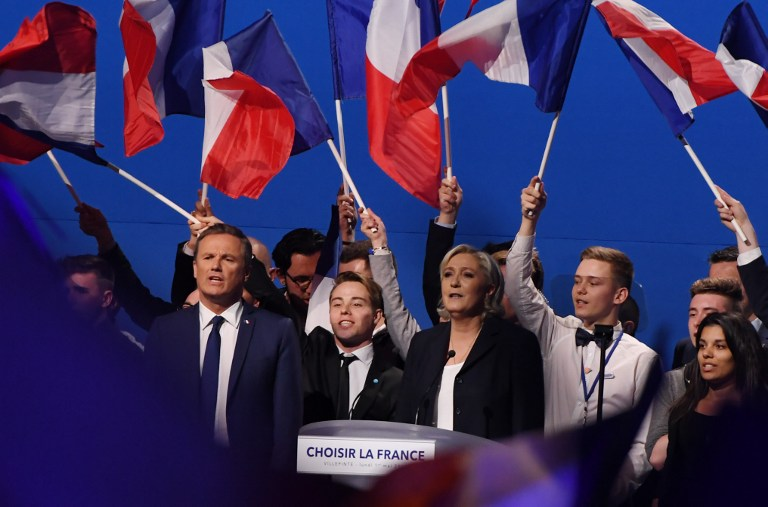 French presidential election candidate for the far-right Front National (FN) party Marine Le Pen (C), flanked by former French presidential election candidate for the right-wing Debout la France (DLF) party Nicolas Dupont-Aignan (L), gestures at the end of her meeting at the Parc des Expositions in Villepinte, on May 1, 2017. (AFP/Alain Jocard)