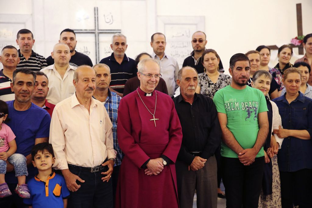 Justin Welby, center, the archbishop of Canterbury, stands with Christian refugees in Amman, Jordan on Tuesday, May 2, 2017.(AP Photo/Sam McNeil)