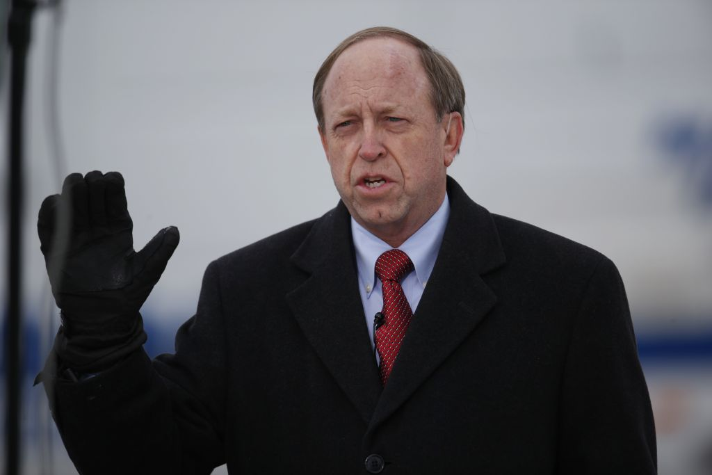 In this Nov. 29, 2015, file photo, Colorado Springs, Colo., Mayor John Suthers talks to a reporter as police investigators gather evidence near the scene of Friday's shooting at a Planned Parenthood clinic. (AP/David Zalubowski, File)