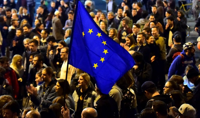 This photo taken on April 9, 2017 shows people marching holding up an EU-flag close to the headquarter of the governor FIDESZ party at Heroes Square as students, teachers of the George Soros-founded Central European University and their sympathizers protest in downtown Budapest. (AFP PHOTO / ATTILA KISBENEDEK)