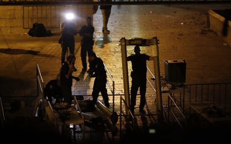 Israeli security forces take down metal detectors at the Lions Gate, near a main entrance to the Temple Mount in Jerusalem's Old City, on July 24, 2017. (AFP/ Ahmad Gharabli)