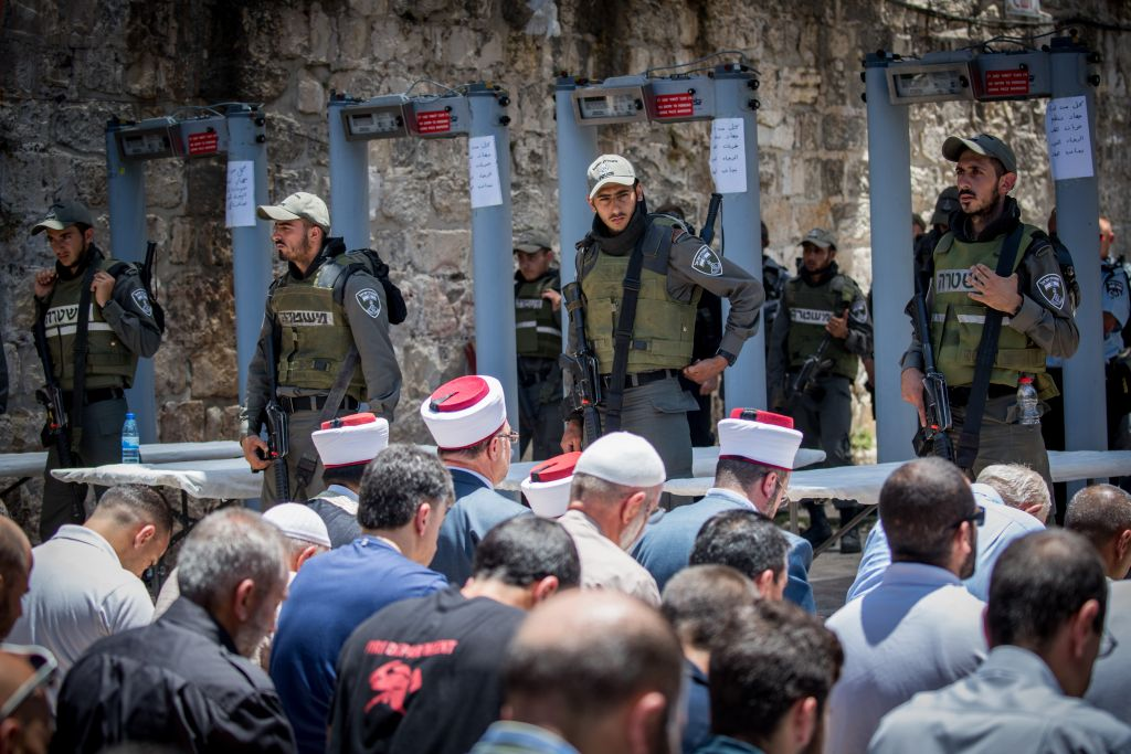 Waqf officials lead Muslim prayers outside the Temple Mount in Jerusalem's Old City on July 16. (Yonatan Sindel/Flash90)
