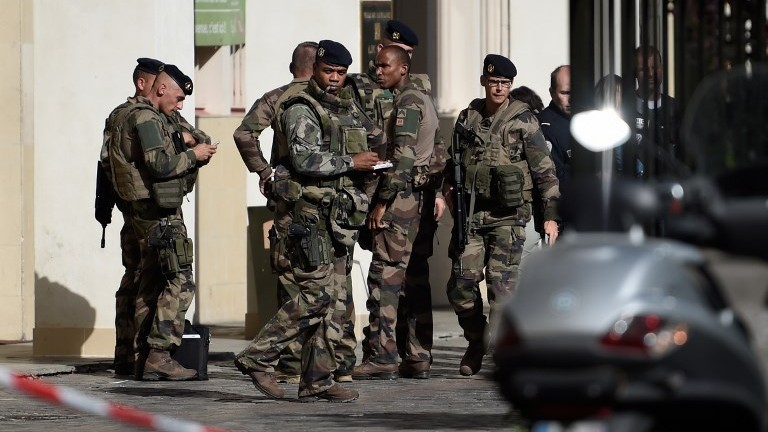 French soldiers gather at the scene of a suspected car-ramming attack on French soldiers on patrol in the Paris suburb of Levallois-Perret on August 9, 2017. (AFP Photo/Stephane De Sakutin)