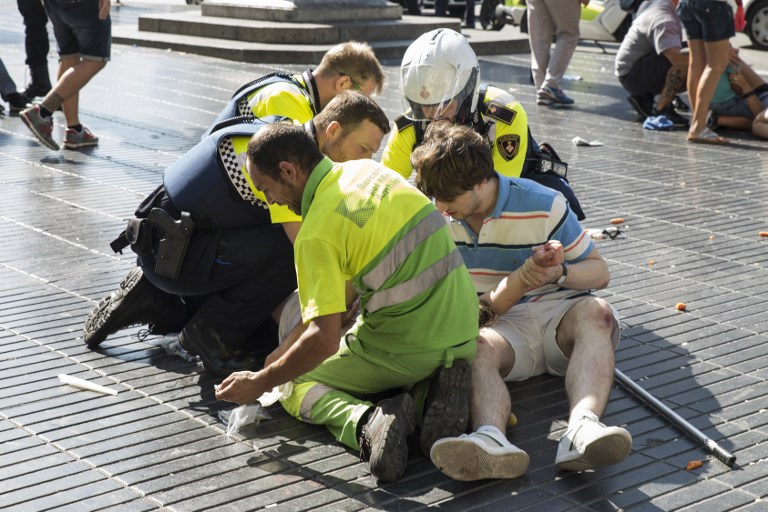 A person is helped by Spanish policemen and two men after a van ploughed into the crowd, killing at least 13 people and injuring around 100 others on the Rambla in Barcelona on August 17, 2017. (AFP PHOTO / Nicolas CARVALHO OCHOA)
