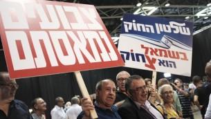 Des militants du Likud avec le député David Bitan, président de la coalition, au centre à droite, pendant un rassemblement de soutien au Premier ministre Benjamin Netanyahu, à Tel Aviv, le 9 août 2017. (Crédit : Tomer Neuberg/Flash90)