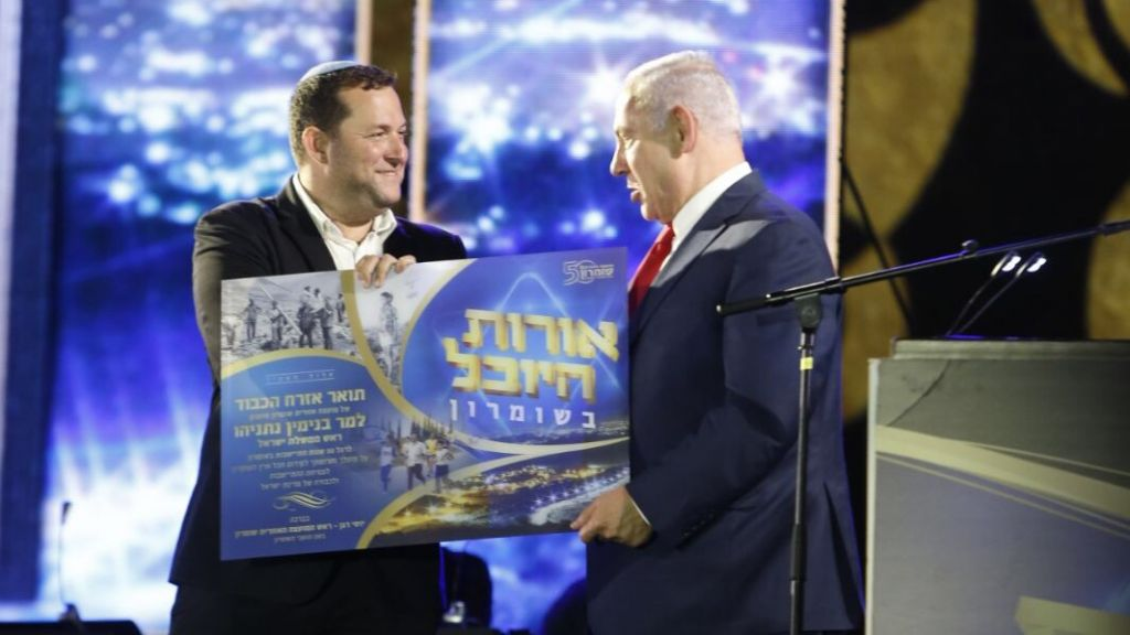 Prime Minister Benjamin Netanyahu (r) with settler leader Yossi Dagan at event commemorating 50 years of settlement in the West Bank, August 28, 2017. (Jacob Magid/Times of Israel)