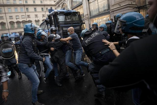 """Starcia z policją: mężczyzna protestuje w Rzymie przeciwko wprowadzeniu """"zielonej przepustki""""."""