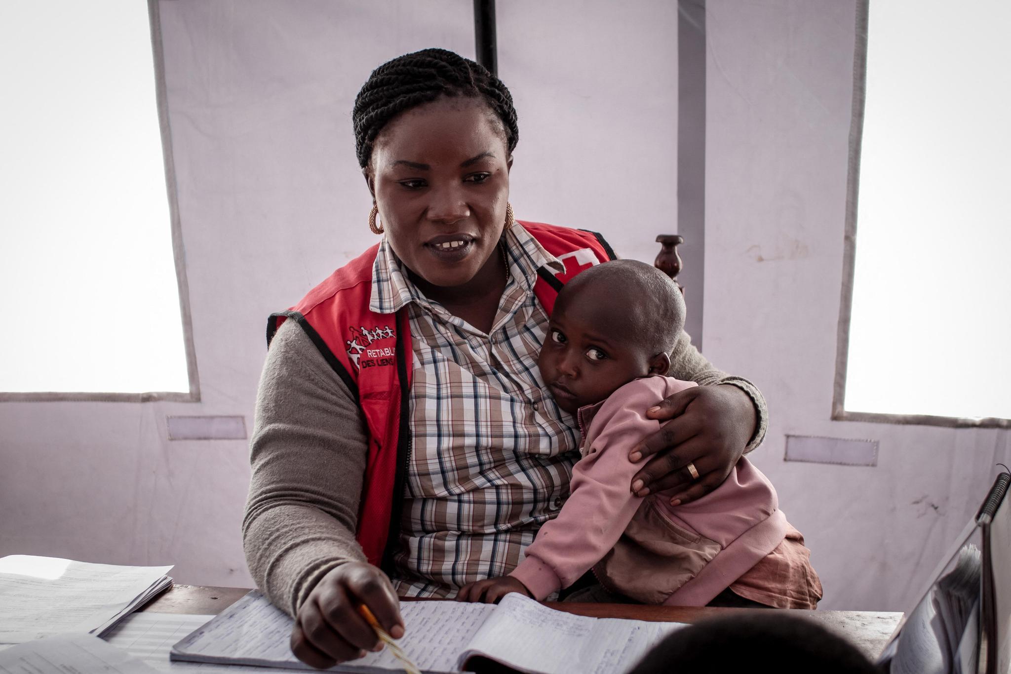 Baraka Bahati, 3ans, dans les bras d'une volontaire de la Croix-Rouge à Minova, le 2juin 2021, après avoir perdu ses parents à Goma.