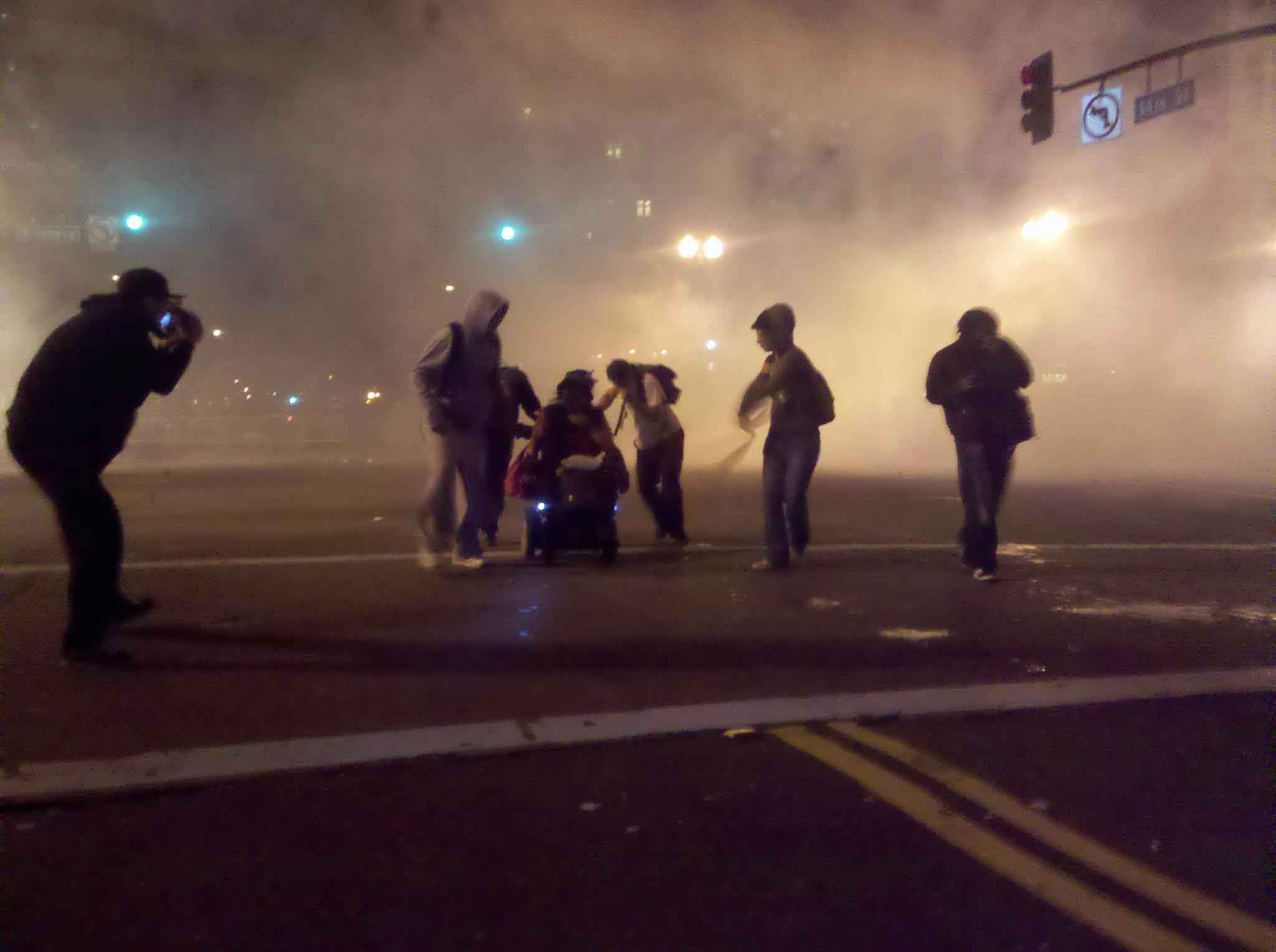 Manifestantes-ayudan-a-una-mujer-en-una-silla-de-ruedas-a-escapar-del-gas-lacrimógeno.-Oakland,-EEUU,-2011.