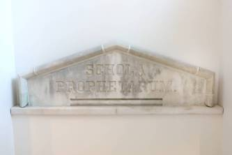 "The historic stone pediment engraved with the Latin term ""schola prophetarum,"" or ""school of prophets,"" was salvaged and is prominently featured in the main stairwell. (Anne Rayner/Vanderbilt)"