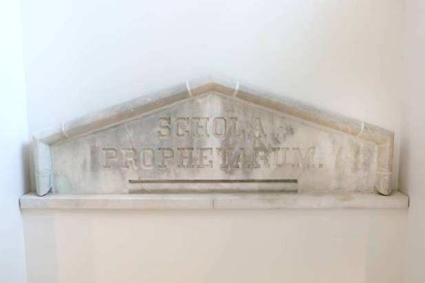 """The historic stone pediment engraved with the Latin term """"schola prophetarum,"""" or """"school of prophets,"""" was salvaged and is prominently featured in the main stairwell. (Anne Rayner/Vanderbilt)"""