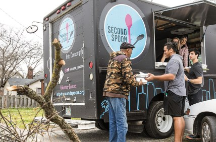 photo of students distributing meals from a food truck